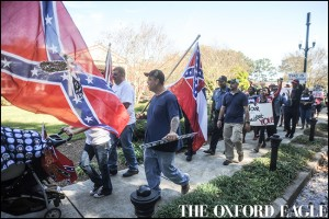 A man carrying a Mississippi state flag is followed by those calling on the University of Mississippi to remove the Mississippi state flag from university grounds, in Oxford, Miss. on Friday, October 16, 2015.