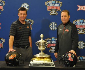 Oklahoma State head coach Mike Gundy, left, and Mississippi head coach Hugh Freeze pose with the Sugar Bowl trophy during a press conference for the Sugar Bowl, in New Orleans, La. on Thursday, December 31, 2015. (AP Photo/Oxford Eagle, Bruce Newman)