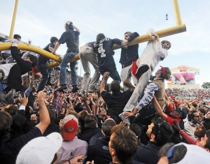 Fans hang on the goalpost while celebrating Ole Miss' win over Alabama on Saturday at Vaught-Hemingway Stadium. (Bruce Newman)