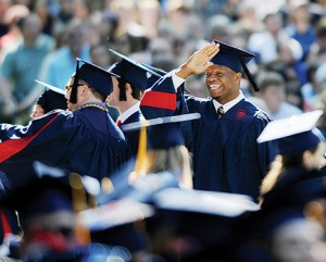 """Bruce Newman Terry Caldwell gives the """"fins up,"""" a signal used by the Ole Miss football team and its fans, during the University of Mississippi commencement ceremony in the Grove on Saturday."""