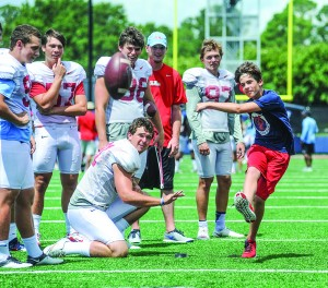 John West Perry, right, the son of the late Dr. Michael Perry and the late Kim Perry, kicks a field goal as Mississippi kicker Nathan Noble (91) holds at football practice in Oxford, Miss. on Tuesday, August 16, 2016. Mississippi hosted the children of people killed in a plane crash last Sunday in Tuscaloosa, Ala. (Bruce Newman, Oxford Eagle via AP)