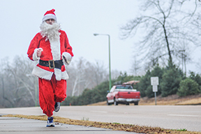 Bret Beauchamp takes a run dressed as Santa Claus, in Oxford, Miss. on Tuesday, December 23, 2014. (AP Photo/Oxford Eagle, Bruce Newman)